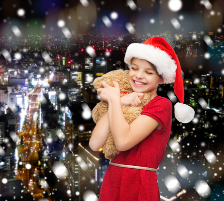 holidays, presents, christmas, childhood and people concept - smiling girl in santa helper hat with teddy bear over snowy night city background photo
