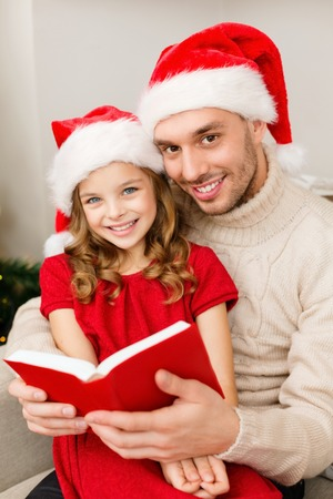 red book: family, christmas, x-mas, happiness and people concept - smiling father and daughter in santa helper hats reading book