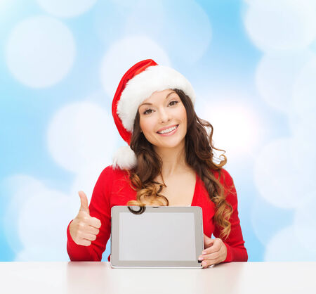 approvement: christmas, holidays, technology and people concept - smiling woman in santa helper hat with tablet pc computer showing thumbs up over blue lights background