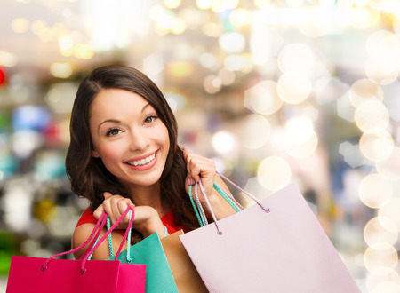 happiness, winter holidays, christmas and people concept - smiling young woman with shopping bags over lights background photo