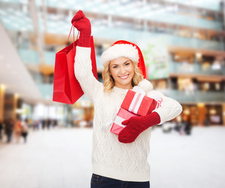 happiness, winter holidays, christmas and people concept - smiling young woman in santa helper hat with gifts and shopping bag over mall background photo