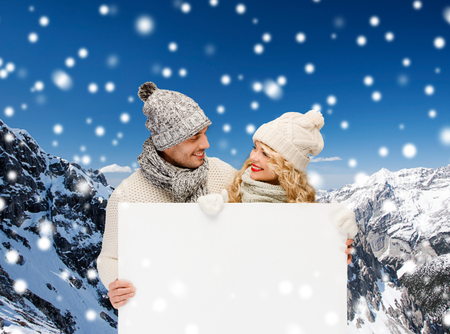 happy couple white background: winter, holidays, christmas, advertisement and people concept - smiling couple in winter clothes with white blank billboard over snowy mountains background