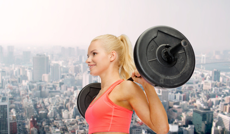 body pump: fitness, sport and dieting concept - smiling sporty woman exercising with barbell