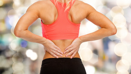 back injury: fitness, healthcare and medicine concept - close up of sporty woman touching her back