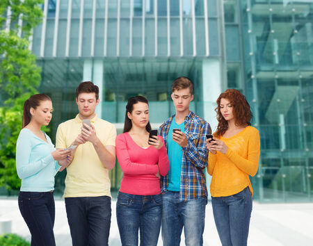 university building: friendship, technology, education, business and people concept - group of serious teenagers with smartphones over campus background Stock Photo
