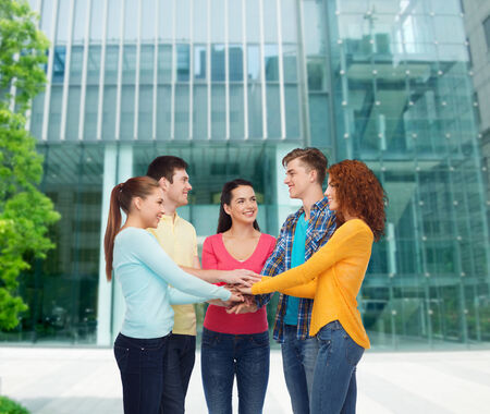 many hands: friendship, education, business, gesture and people concept - group of smiling teenagers with hands on top of each other over campus background