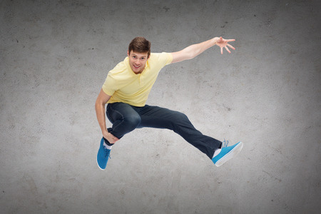 man flying: happiness, freedom, movement and people concept - smiling young man jumping in air over concrete wall background