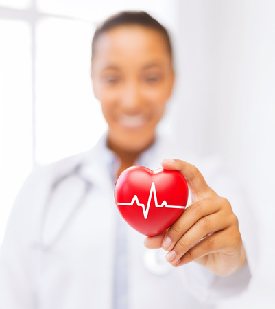 transplantation: healthcare and medicine concept - female african american doctor holding red heart with ecg line