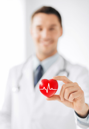 healthcare and medicine concept - male doctor holding red heart with ecg line photo