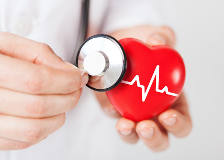 illness: healthcare and medicine concept - close up of male doctor hands holding red heart with ecg line and stethoscope