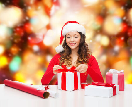 christmas, holidays, celebration, decoration and people concept - smiling woman in santa helper hat with decorating paper packing gift boxes over red lights background photo