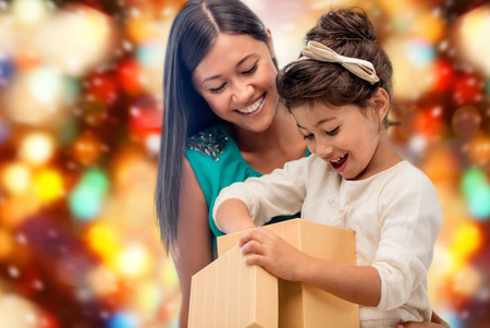 little girl surprised: christmas, holidays, celebration, family and people concept - happy mother and child girl with gift box over red lights background Stock Photo