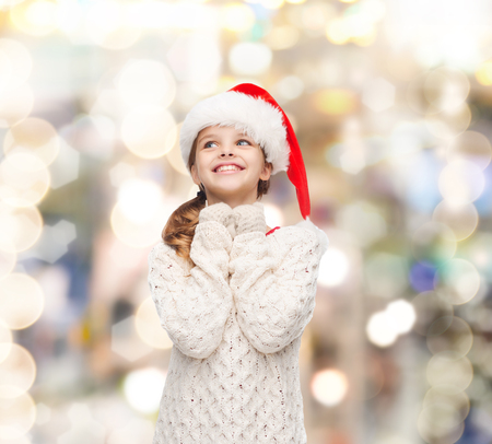 christmas, holidays, childhood and people concept - smiling girl in santa helper hat over lights background photo