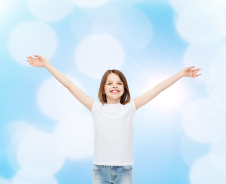 stretched out: advertising, gesture, childhood and people - smiling little girl in white blank t-shirt with stretched out arms over blue background Stock Photo