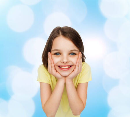 happiness and people concept - smiling little girl holding head over white background photo