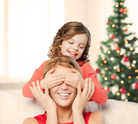 guess: christmas, x-mas, winter, happiness concept - mother and daughter making a joke