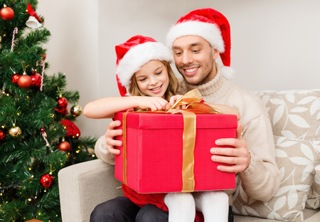 huge christmas tree: family, christmas, x-mas, happiness and people concept - smiling father and daughter in santa helper hats opening gift box