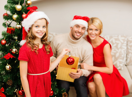 family, christmas, x-mas, happiness and people concept - smiling family in santa helper hats decorating christmas tree photo