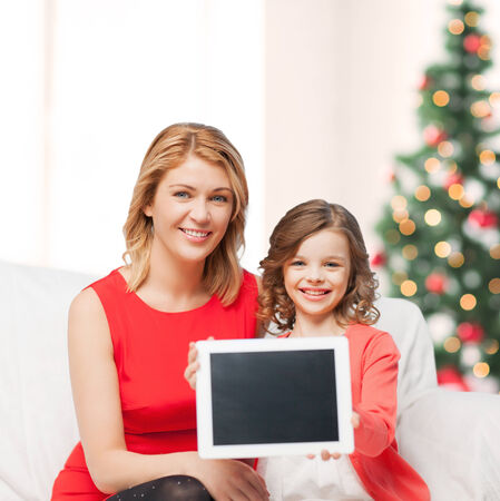 christmas, x-mas, happiness, advertisement concept - mother and daughter with tablet pc showing blank screen photo