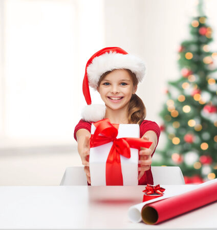 christmas, x-mas, winter, happiness concept - smiling girl in santa helper hat with gift box and wrapping paper photo