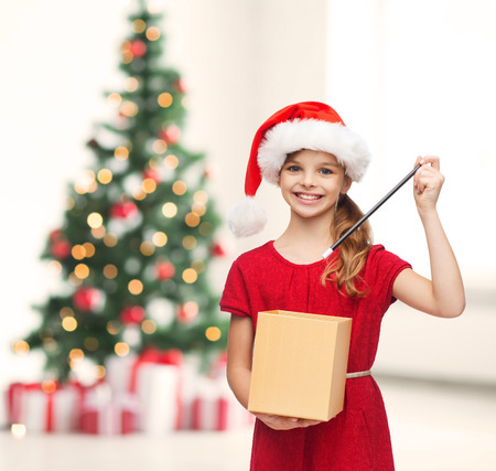 christmas, x-mas, winter, happiness concept - smiling girl in santa helper hat with gift box and magic wand photo