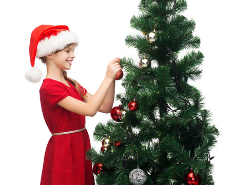 christmas, x-mas, winter, happiness concept - smiling girl in santa helper hat decorating a tree photo