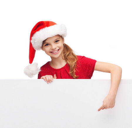 christmas, xmas, holidays and advertisement concept - happy girl child in santa helper hat pointing finger on blank white board photo