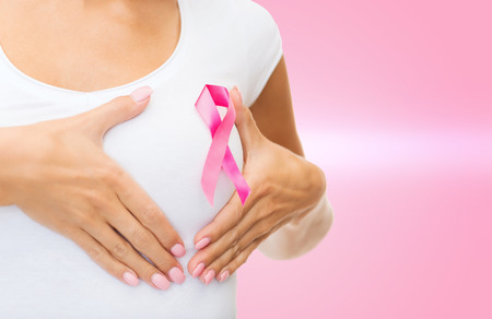 breast examination: healthcare and medicine concept - woman in blank t-shirt with pink breast cancer awareness ribbon checking breast
