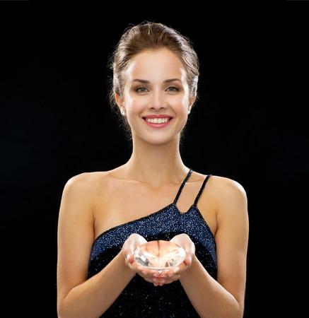 caras emociones: gente, fiestas y glamour concepto - mujer sonriente en traje de noche sobre fondo negro