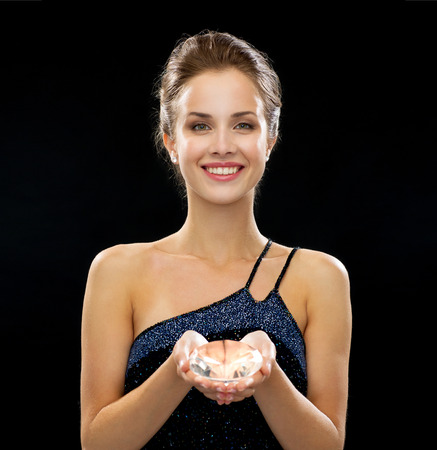 people, holidays and glamor concept - smiling woman in evening dress over black 版權商用圖片