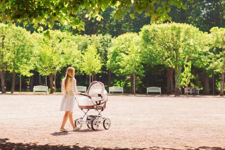 家族、子供と親のコンセプト - 後ろから歩いて公園のベビーカーと幸せな母