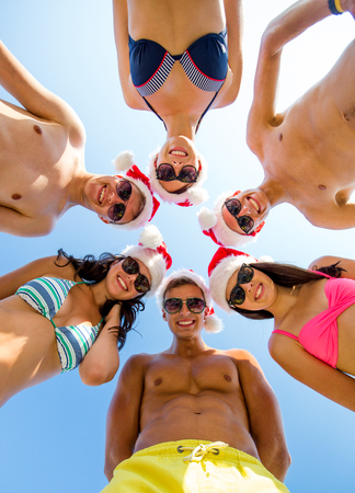 suntanned: friendship, christmas, summer vacation, holidays and people concept - group of smiling friends wearing swimwear and santa helper hats standing in circle over blue sky