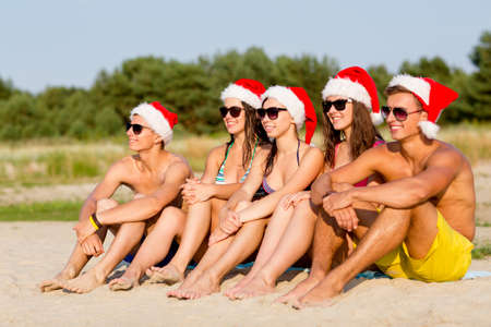 friendship, happiness, summer vacation, holidays and people concept - group of friends in santa helper hats sitting on beach photo