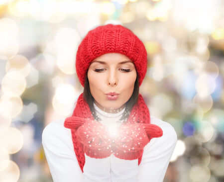 red snowflake background: happiness, winter holidays, christmas and people concept - smiling young woman in red hat, scarf and mittens over lights background Stock Photo