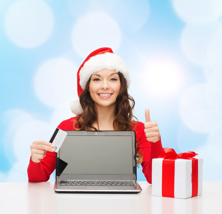 approvement: christmas, holidays, technology and shopping concept - smiling woman in santa helper hat with credit card, gift box and laptop computer showing thumbs up gesture over blue lights background Stock Photo