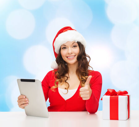 approvement: christmas, holidays, technology, gesture and people concept - smiling woman in santa helper hat with gift box and tablet pc computer showing thumbs up over blue lights background