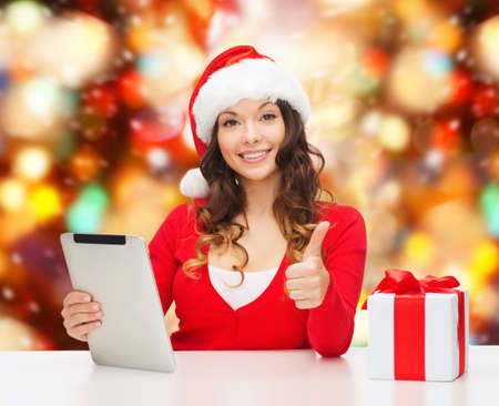 approvement: christmas, holidays, technology, gesture and people concept - smiling woman in santa helper hat with gift box and tablet pc computer showing thumbs up over red lights background
