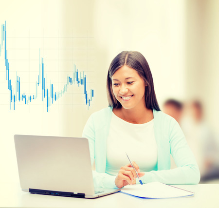 business, money and technology concept - asian businesswoman with laptop, documents and forex chart in office photo