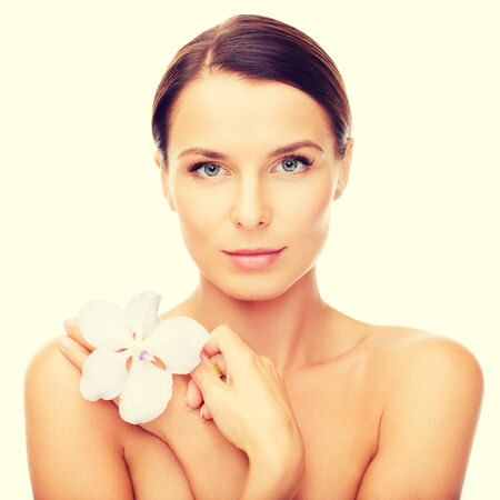 smooth skin: health and beauty concept - relaxed woman with orhid flower