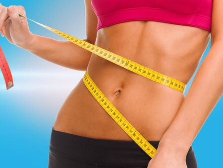 six packs: sport, fitness and diet concept - close up of trained belly with measuring tape