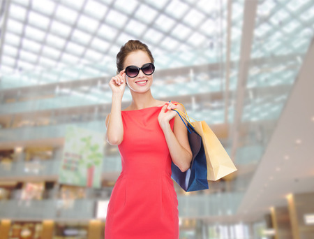 shopping, sale, christmas and holiday concept - smiling elegant woman in red dress and sunglasses with shopping bags Stock Photo