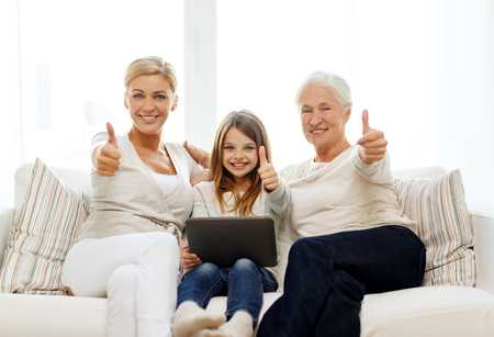 family couch: family, generation, technology and people concept - smiling mother, daughter and grandmother with tablet pc computer sitting on couch at home