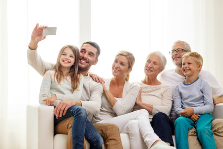 family, happiness, generation and people concept - happy family sitting on couch and making selfie with smartphone at home photo