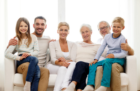 grandparents: family, happiness, generation and people concept - happy family sitting on couch at home