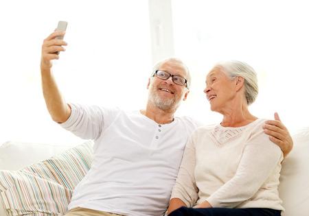 vejez feliz: la familia, la tecnología, la edad y el concepto de la gente - la feliz pareja senior con la toma de teléfono inteligente Autofoto en casa Foto de archivo