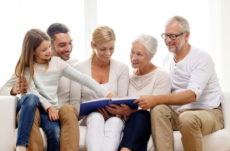 Familie, geluk, generatie en mensenconcept - gelukkige familie met boek of fotoalbum op de bank thuis zitten Stockfoto
