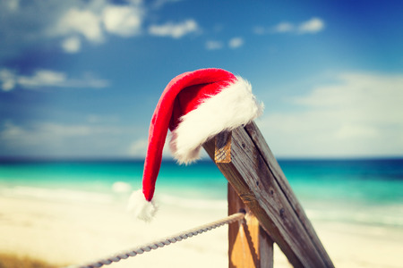tropical christmas: beach, summer, vacations, christmas and sea concept - close up of santa helper hat on beach