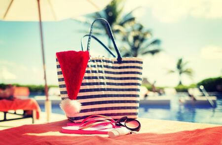summer holidays, christmas and vacation concept - santa helper hat, bag, sunscreen and sunglasses photo