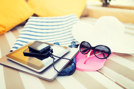 mobile accessories: beach, summer vacation and technology concept - close up of tablet pc, notebook, smartphone and summer accessories on beach