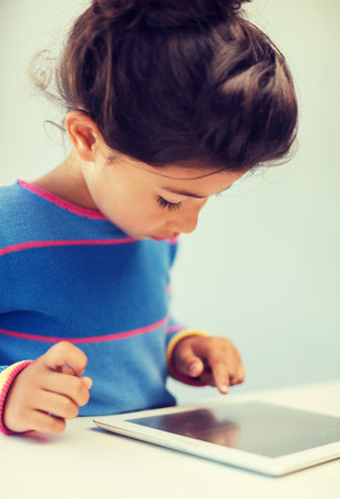 latin child: education, technology and internet concept - little girl with tablet pc Stock Photo
